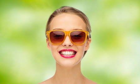 summer beauty: beauty, people, accessory and fashion concept - smiling young woman in sunglasses with pink lipstick on lips over green summer background