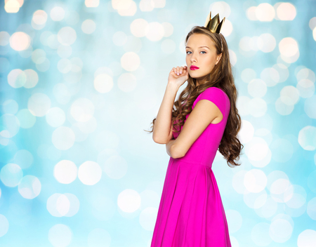 arrogant teen: people, holidays and fashion concept - young woman or teen girl in pink dress and princess crown over blue holidays lights background