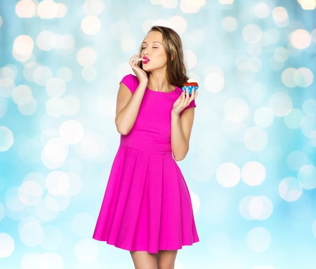 muffin: people, holidays, party, junk food and celebration concept - happy young woman in pink dress eating birthday cupcake over blue holidays lights background
