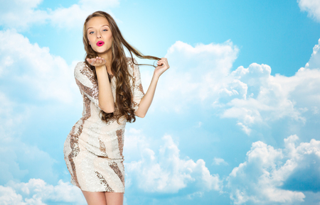 kiss: people, style, holidays, hairstyle and fashion concept - happy young woman or teen girl in fancy dress with sequins and long wavy hair sending blow kiss over blue sky and clouds background
