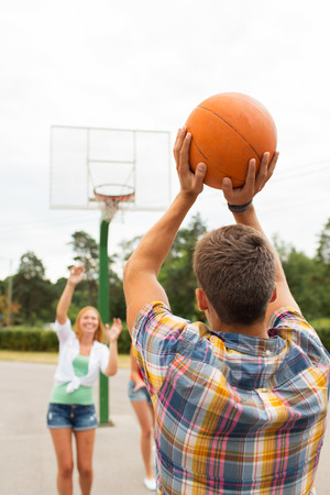 summer sport: summer vacation, sport, games and friendship concept - group of happy teenagers playing basketball outdoors from back