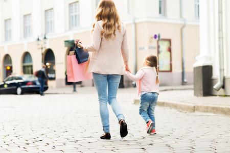 Ausverkauf, Konsum und Menschen Konzept - Nahaufnahme von Mutter und Kind mit Einkaufstüten zu Fuß entlang Stadtstraße Standard-Bild