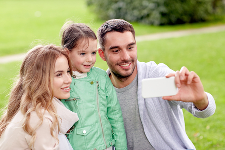 photographing: family, childhood, technology and people concept - happy father, mother and little daughter taking selfie by smartphone in park