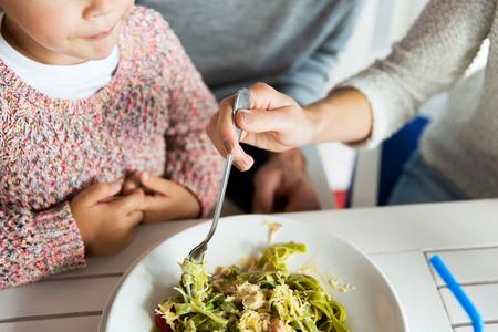 familie, ouderschap, voedsel en mensen concept - close-up van de familie eten pasta voor het diner in het restaurant of cafe