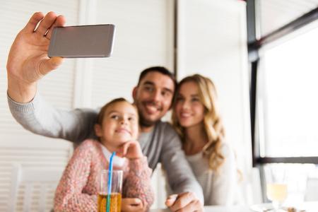 la familia, la paternidad, la tecnología y el concepto de la gente - cerca de la feliz madre, el padre y la niña que tiene la cena y tomar autofoto por teléfono inteligente en el restaurante