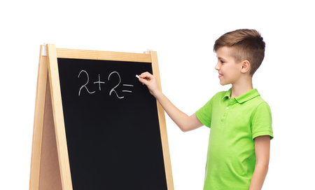 pre adolescent boy: childhood, education, school, advertisement and people concept - happy smiling boy in green polo t-shirt solving math task on blank school chalk blackboard