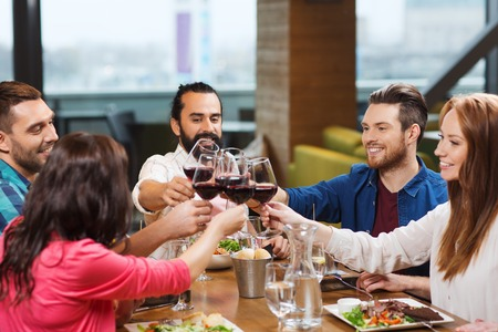 leisure, celebration, food and drinks, people and holidays concept - smiling friends having dinner and drinking red wine at restaurant Imagens