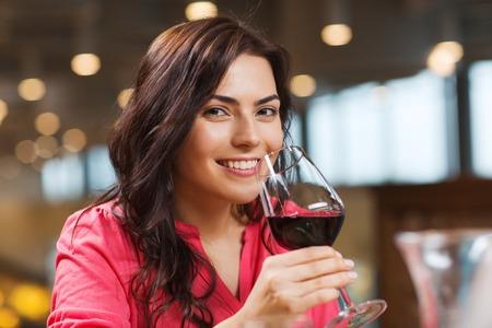 tomando vino: ocio, bebidas, degustación, la gente y el concepto de vacaciones - Mujer sonriente que bebe vino tinto en el restaurante Foto de archivo
