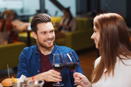 dinner food: leisure, eating, food and drinks, people and holidays concept - smiling couple having dinner and drinking red wine at restaurant Stock Photo