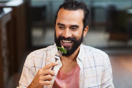 hombre comiendo: ocio, comida, comer, la gente y el concepto de vacaciones - hombre feliz con los amigos que tienen la cena en el restaurante
