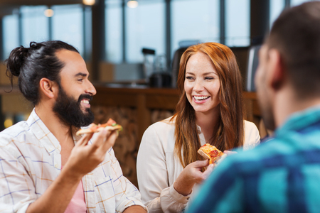 eating dinner: leisure, food and drinks, people and holidays concept - smiling friends eating pizza and drinking beer at restaurant or pub Stock Photo
