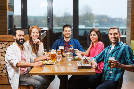 holiday gathering: leisure, eating, food and drinks, people and holidays concept - smiling friends having dinner and drinking beer at restaurant or pub