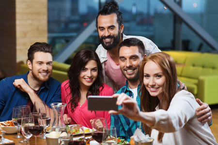friend: leisure,technology, friendship, people and holidays concept - happy friends having dinner and taking selfie by smartphone at restaurant Stock Photo