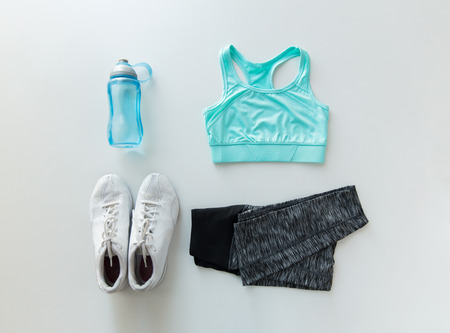 sport, fitness, healthy lifestyle and objects concept - close up of female sports clothing and bottle set