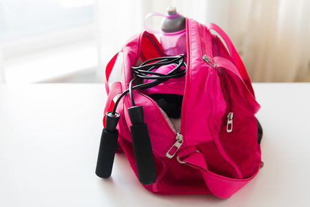 sport, fitness, healthy lifestyle and objects concept - close up of female sports stuff in bag and skipping rope Stock Photo