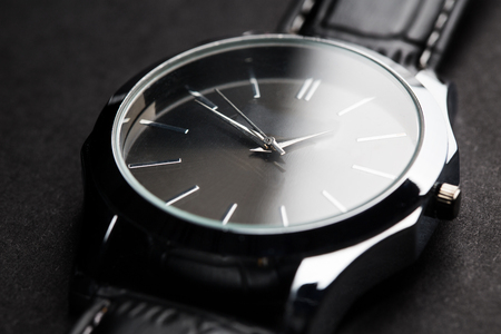 punctuality: time, punctuality, object and accessory concept - close up of black classic male wristwatch