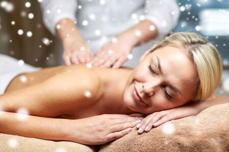 massagist: people, beauty, spa, winter and relaxation concept - close up of beautiful young woman lying with closed eyes and having hand back massage in spa salon with snow effect
