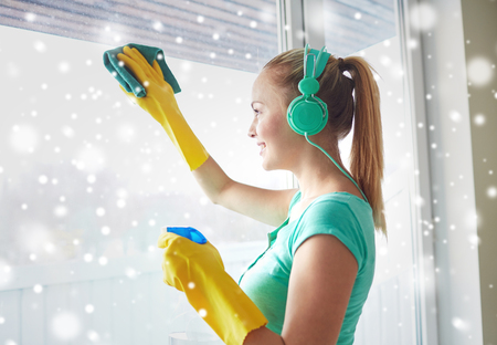 cleanser: people, housework and housekeeping concept - happy woman in headphones listening to music and cleaning window with cleanser at home over snow effect Stock Photo