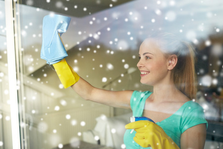 cleanser: people, housework and housekeeping concept - happy woman in gloves cleaning window with rag and cleanser spray at home over snow effect