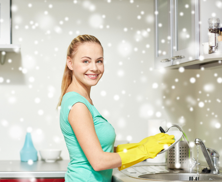 dish washing: people, housework and housekeeping concept - happy woman in protective gloves washing dishes at home kitchen over snow effect