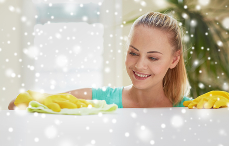 people, housework and housekeeping concept - happy woman cleaning table at home kitchen over snow effect Stock fotó