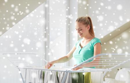 Menschen, Hausarbeit, Wäscherei und Reinigungskonzept - glückliche Frau, die Kleidung auf Trockner zu Hause über Schnee-Effekt hängen