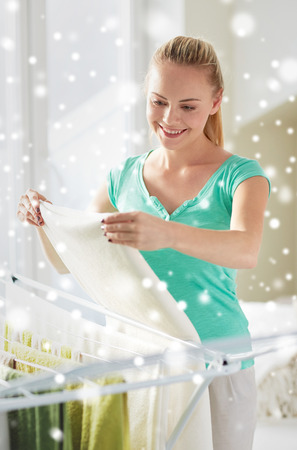 laundry concept: people, housework, laundry and housekeeping concept - happy woman hanging clothes on dryer at home over snow effect