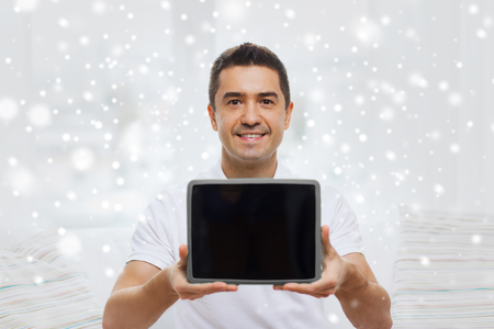 mid distance: technology, people and lifestyle, distance learning concept - happy man showing tablet pc computer black blank screen at home over snow effect