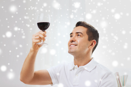 degustating: profession, drinks, leisure and people concept - happy man drinking red wine from glass at home over snow effect Stock Photo