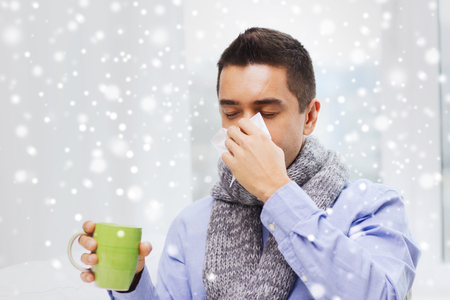 illness: healthcare, flu, people, rhinitis and medicine concept - ill man blowing his nose with paper napkin and drinking tea at home over snow effect