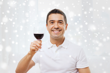degustating: profession, drinks, leisure, holidays and people concept - happy man drinking red wine from glass at home over snow effect