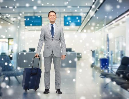zakenreis, reizen, bagage en mensenconcept - gelukkige zakenman in kostuum met reiszak over luchthavenachtergrond en sneeuweffect Stockfoto
