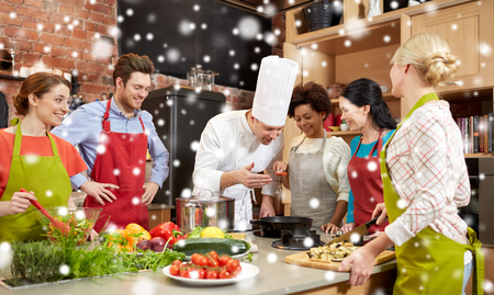 degustating: cooking class, culinary, food and people concept - happy group of friends and male chef cook cooking in kitchen over snow effect