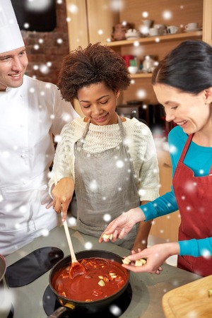 souse: cooking class, culinary, food and people concept - happy group of women and male chef cook cooking tomato souse in kitchen over snow effect