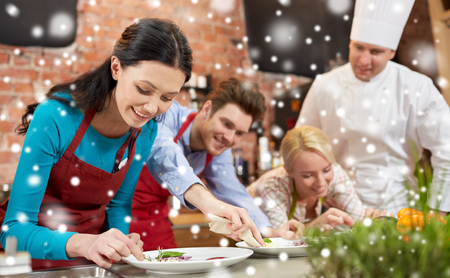 class: cooking class, culinary, food and people concept - happy couple and male chef cook cooking and decorating plates in kitchen over snow effect