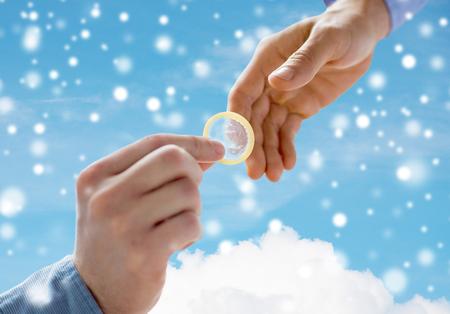 sexual education: personas, homosexualidad, sexo seguro, la educación sexual y el concepto de la caridad - Cerca de feliz pareja manos de los homosexuales varones que dan condón sobre el cielo azul y nubes de fondo y el efecto de la nieve Foto de archivo