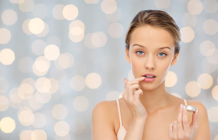 beauty, people and lip care concept - young woman applying lip balm to her lips over holidays lights background