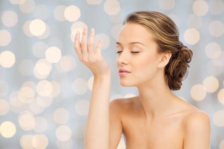 la belleza, el aroma, la gente y el concepto del cuidado del cuerpo - mujer joven que huele el perfume de la muñeca de la mano durante las vacaciones de fondo de las luces Foto de archivo