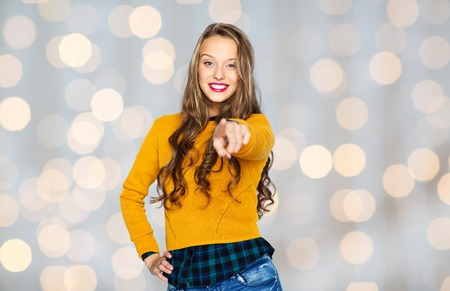 trendy girl: people, style and fashion concept - happy young woman or teen girl in casual clothes pointing finger on you over holidays lights background Stock Photo