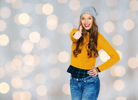 posing  agree: people, style and fashion concept - happy young woman or teen girl in casual clothes and hipster hat showing thumbs up over holidays lights background