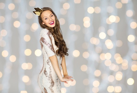 the majesty: people, holidays and celebration concept - happy young woman or teen girl in party dress and princess crown over holidays lights background