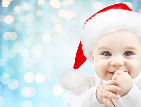 babyhood: christmas, babyhood, childhood and people concept - happy baby in santa hat over blue holidays lights background Stock Photo