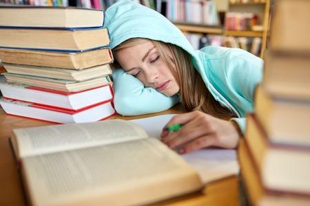 사람들, 교육, 세션, 시험 및 학교 개념 - 피곤 된 학생 소녀 또는 젊은 여자와 라이브러리에서 자 고하는 책