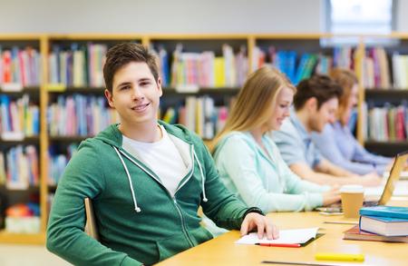 ludzie, wiedza, edukacja i koncepcji szkoły - szczęśliwy chłopiec studentów czytania książki w bibliotece