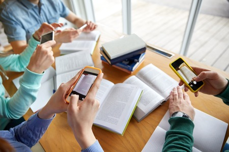 making up: people, education, technology and exam concept - close up of students with smartphones taking picture of books page and making cheat sheet in school library Stock Photo