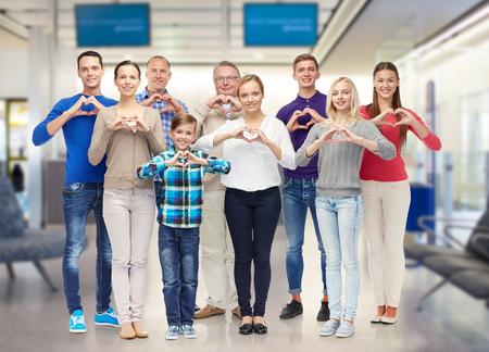 gesto, los viajes, el turismo y la gente concepto - familia feliz que muestra el corazón shape mano sobre fondo aeropuerto sala de espera