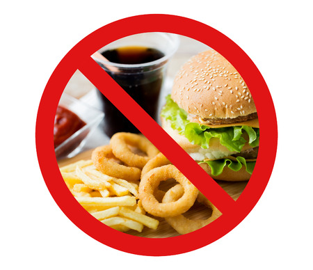 low fat: fast food, low carb diet, fattening and unhealthy eating concept - close up of hamburger or cheeseburger, deep-fried squid rings and french fries behind no symbol or circle-backslash prohibition sign