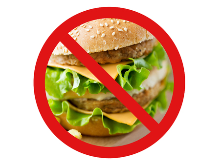 fast food, low carb diet, fattening and unhealthy eating concept - close up of hamburger or cheeseburger behind no symbol or circle-backslash prohibition sign