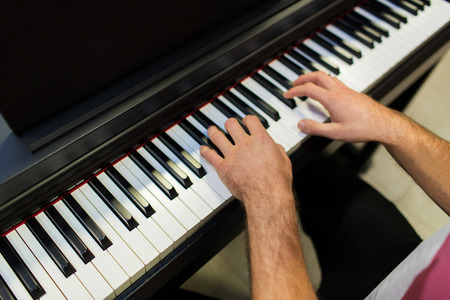 entertainment concept: music, people, art, musical instruments and entertainment concept - close up of male hands playing piano Stock Photo