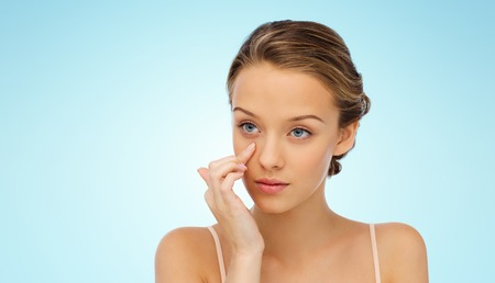 eye cream: beauty, people, cosmetics, skincare and health concept - young woman applying cream to her face over blue background